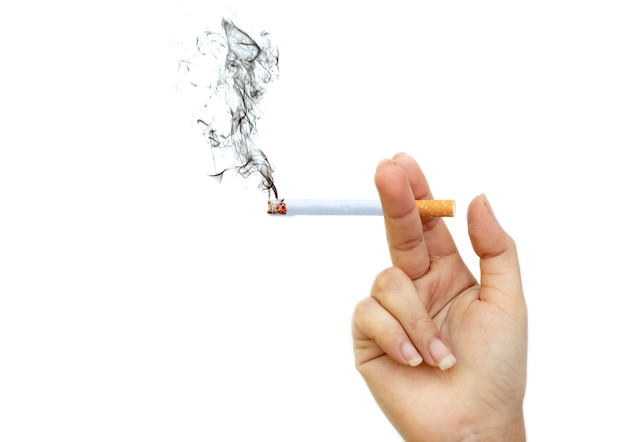 Image of cigarette burns with smoke in lady's hand at isolated white background