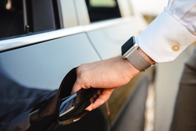 Image closeup of caucasian man wearing wrist watch, opening door of luxury black car