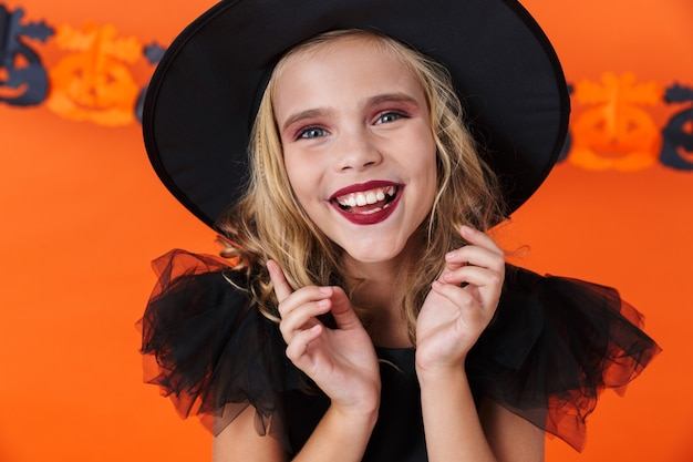 Image closeup of nice caucasian woman in black halloween costume laughing and looking at camera isolated over orange pumpkin wall