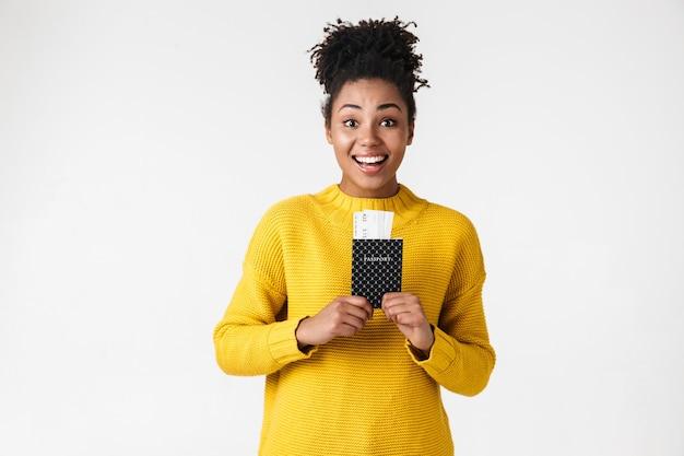 Изображение крупным планом раздраженной афро-американской женщины, смотрящей в камеру с паспортом и билетами над белой