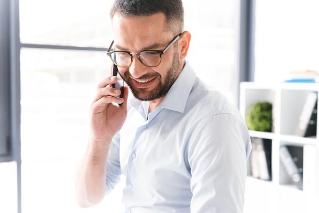 オフィスで働いている間、ビジネスについて黒のスマートフォンで話しているフォーマルな服装でひげを生やした男の画像のクローズアップ