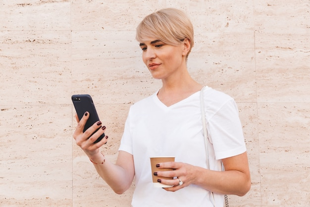 Изображение крупным планом кавказской белокурой женщины в белой футболке, использующей мобильный телефон, стоя у бежевой стены на открытом воздухе летом и пьющей кофе из бумажного стаканчика