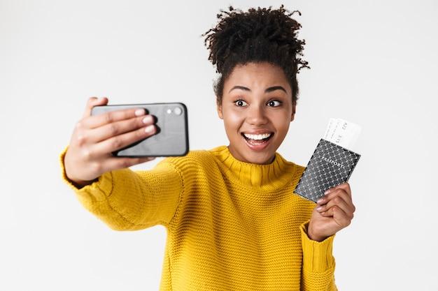 Изображение крупным планом довольно афро-американской женщины, смотрящей на смартфон, держа в руках паспорт и билеты над белой