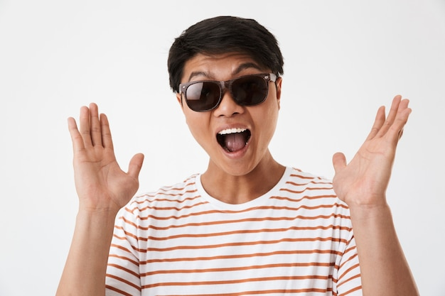 Image closeup of satisfied joyful asian man wearing striped t-shirt and black eyeglasses smiling or screaming in surprise, isolated. concept of emotions