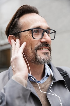 Image closeup of smiling businessman in eyeglasses using earphones while standing near office building