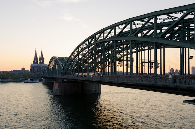 Image of cologne with cologne cathedral and railway during sunset in germany.