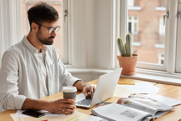Image of concentrated unshaven businessman watches important webinar or online conference