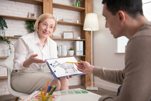Image concept. successful mature psychologist sharing her observation while man pointing at image
