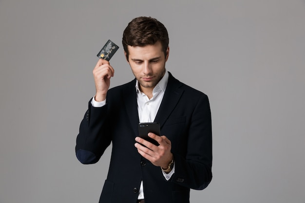 Image of confident businessman 30s in suit using credit card and mobile phone, isolated over gray wall