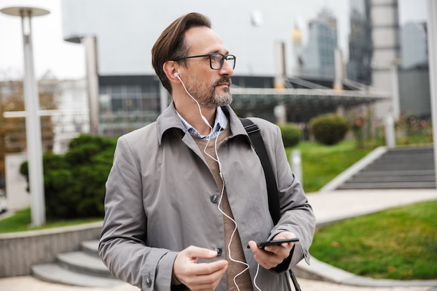 Image of confident businessman in eyeglasses using cellphone and earphones while walking at city street