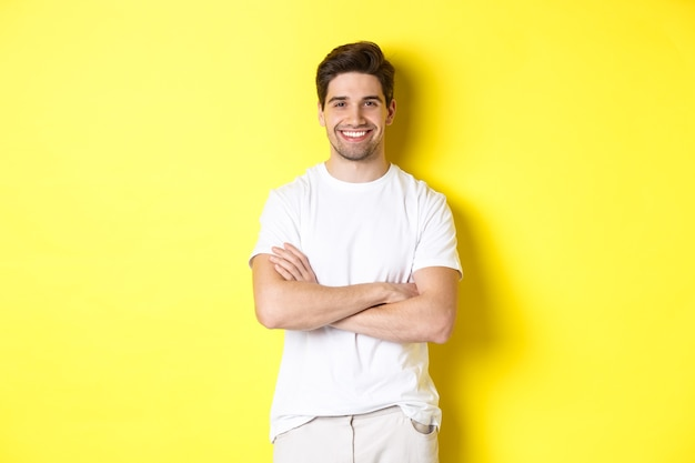Image of confident caucasian man smiling pleased, holding hands crossed on chest and looking satisfied, standing over yellow background.