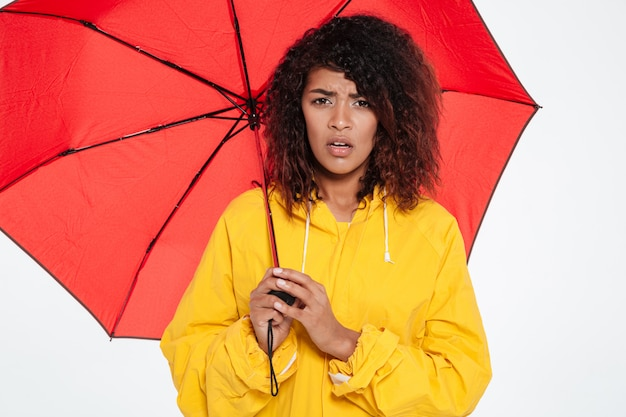 Image of confused african woman in raincoat hiding under umbrella