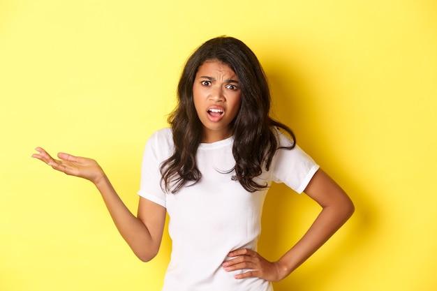 Immagine di una ragazza afroamericana confusa e infastidita che discute alzando la mano