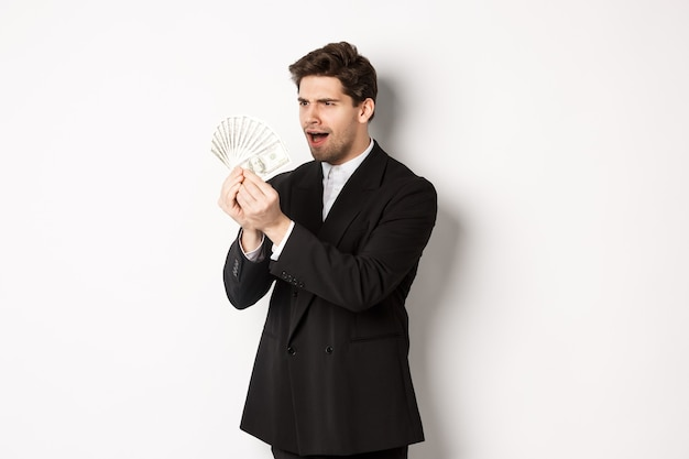 Image of confused businessman looking at fake money, standing over white background in black suit
