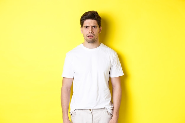 Image of confused and puzzled man cant understand something, frowning and looking shocked, standing over yellow background.