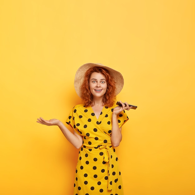 Image of confused surprised beautiful redhead lady raises palm, holds mobile phone, rejoices new purchase, wears straw hat and polka dot yellow dress. feminity, lifestyle