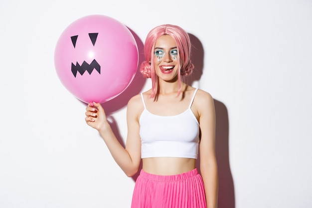 Image of coquettish party girl with bright makeup, wearing pink wig, holding balloon with jack-o'-lantern face, celebrating halloween.