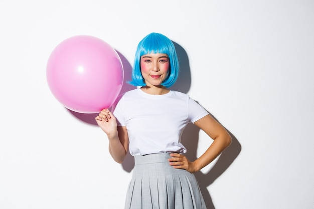 Image of coquettish sassy asian woman in blue wig, dressed-up for party, holding large pink balloon and smiling confident at camera.