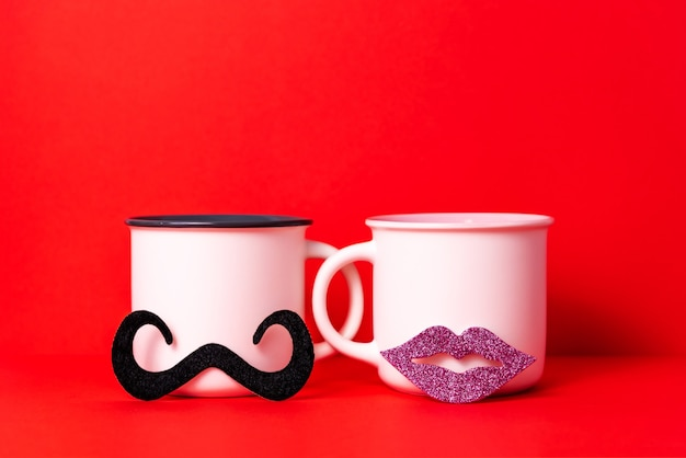 Image of couple white cups of coffee with female lips and male mustache, dating on valentine's day celebration concept.