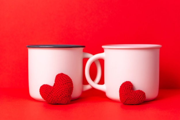 Image of couple white cups of coffee with two knittled hearts, dating on valentine's day celebration concept.