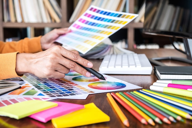 Image of creative graphic designer working on color selection and drawing on graphics tablet