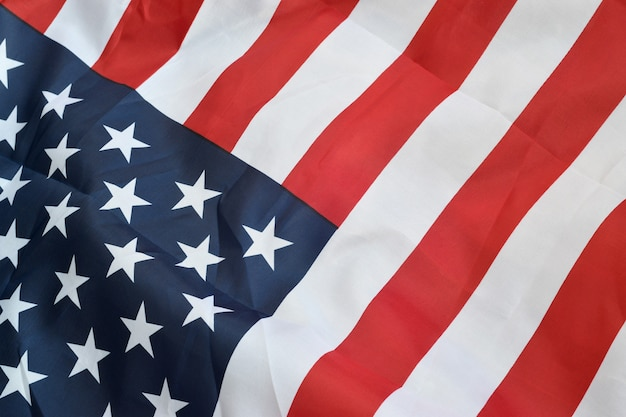 Image of a crumpled american flag with many folds waving in the wind