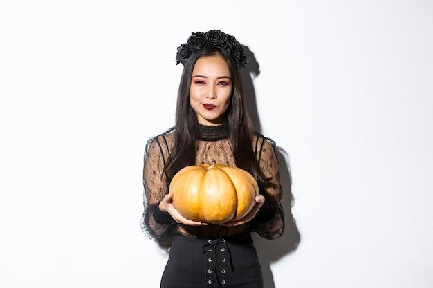 Immagine di astuta donna asiatica in abito nero, impersonando strega cattiva su halloween, tenendo grande zucca, in piedi su sfondo bianco.
