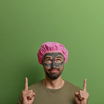 Image of curious adult bearded man with beauty mud mask on face, indicates upwards with both index fingers, advertises cosmetic product, wears bath cap, looks above, isolated on green wall