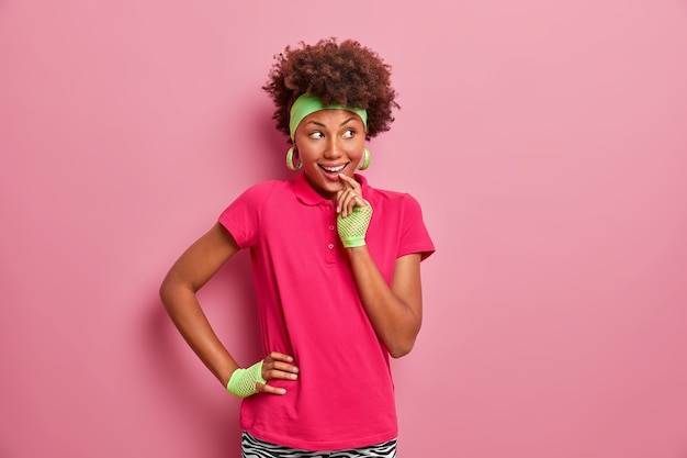 L'immagine della ragazza dai capelli ricci ha un'espressione allegra astuta, guarda con l'intenzione di attuare il piano, vestita con abiti casual