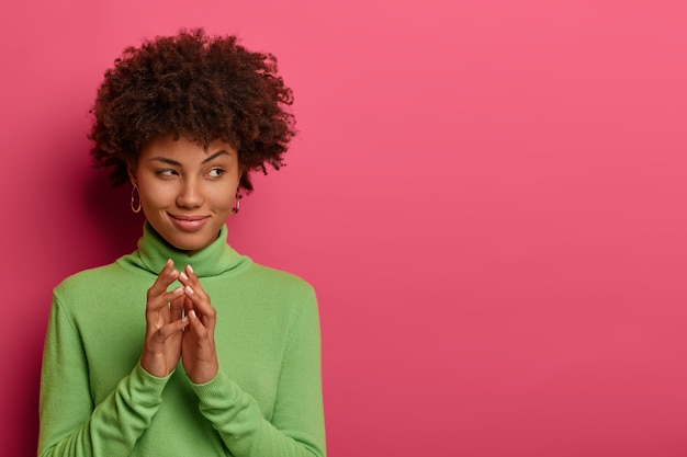 Image of curly haired young woman gestures with intention, concentrated aside, schemes interesting event, dressed in green turtleneck, has sly expression, models over rosy wall, copy space aside