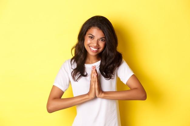 Immagine di una graziosa donna afroamericana che ringrazia e sorride stringendosi le mani