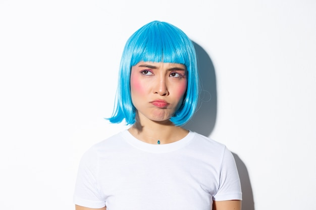 Image of cute asian girl in blue wig looking disappointed or jealous, sulking while stare at upper left corner