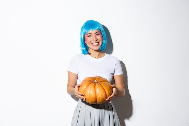 Image of cute asian girl giving you pumpkin for halloween party, wearing blue wig, standing.
