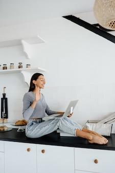 Immagine della donna bruna carina seduta sul tavolo in cucina e utilizzando il computer portatile