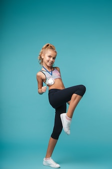 Image of a cute little girl child with a medal posing isolated over blue wall showing winner gesture.