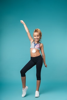 Image of a cute little girl child with a medal posing isolated over blue wall.