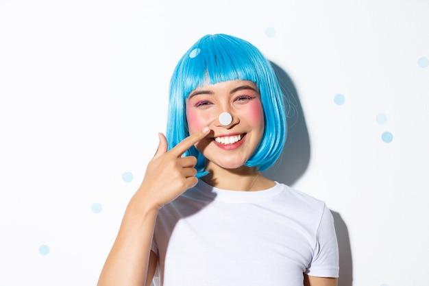 Immagine della ragazza asiatica carina e sciocca con i coriandoli sul naso sorridendo e guardando felice, indossando la parrucca blu per la festa di halloween.