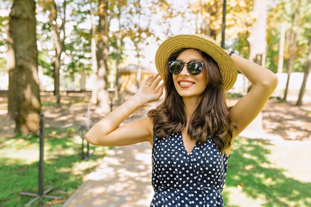 Image of cute woman with dark short hair dressed in dress is walking in the park with charming smile. she is wearing summer hat and black sunglasses.
