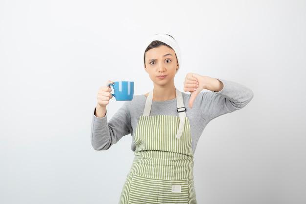 Immagine di una giovane donna carina in grembiule con una tazza blu che mostra un pollice verso il basso