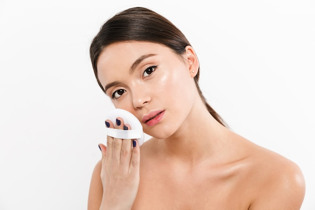 Image of dark-haired woman with soft healthy skin, applying makeup with cosmetic sponge isolated over white