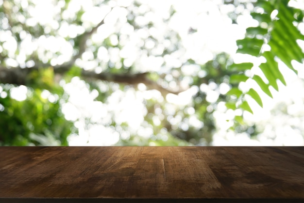 Image of dark wooden table in front of abstract blurred background of outdoor garden lights. can be used for display or montage your products.mock up for display of product