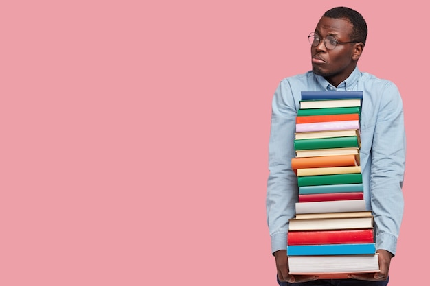 Image of dejected black man looks with miserable expression aside, holds pile of books, dressed in formal clothes
