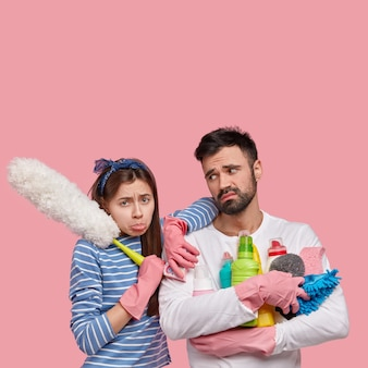 Image of dejected wife and husband clean at home, do spring cleaning, feel fatigue, stand closely to each other, hold detergents