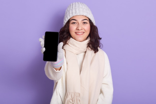 Image of delighted attractive model holding her switched off smartphone in one hand, showing it, blank screen, being in good mood, looking directly at camera, isolated on lilac.