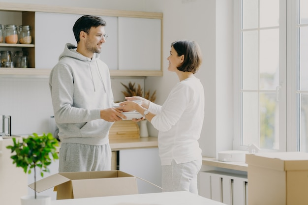 Image of delighted family couple unpack utensils with carton boxes, move in new home, pose against kitchen interior, looks happily at each other, busy unpacking different home stuff. householding