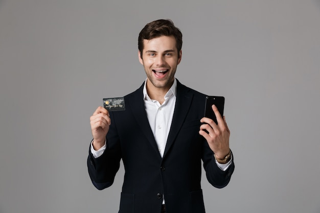 Image of delighted man 30s in business suit holding black mobile phone and credit card, isolated over gray wall