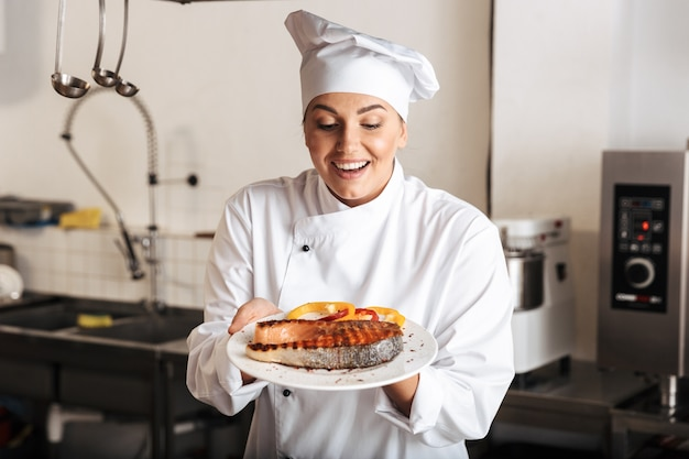 Image of delighted woman chef wearing white uniform, holding plate with grilled fish in kitchen at the restaurant