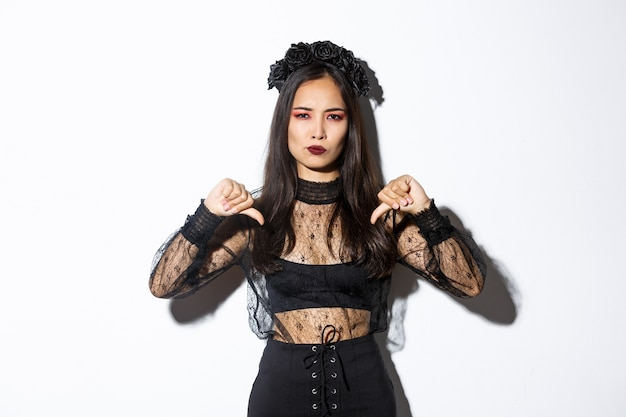 Image of disappointed asian woman in halloween dress of gothic undead girl showing thumbs-down, dislike and disagree with something bad, standing over white background.