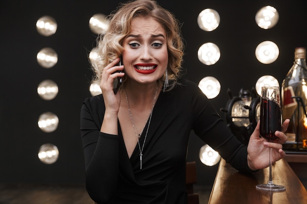 Image of disappointed blonde woman wearing elegant dress talking on cellphone and drinking red wine in bar