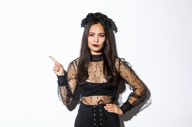 Immagine di donna asiatica delusa e scettica in costume da strega che si lamenta di qualcosa, indicando l'angolo in alto a sinistra e fa una smorfia insoddisfatta, in piedi su sfondo bianco in abito di halloween.